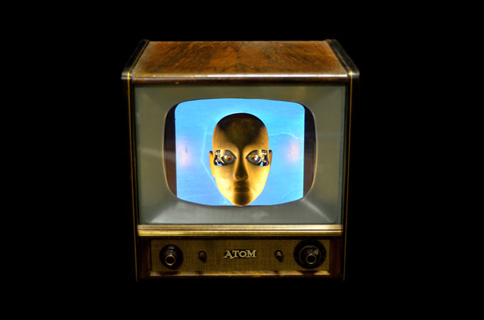 Image of old fashioned TV with a picture of a manikin's face on a blue screen on a black background