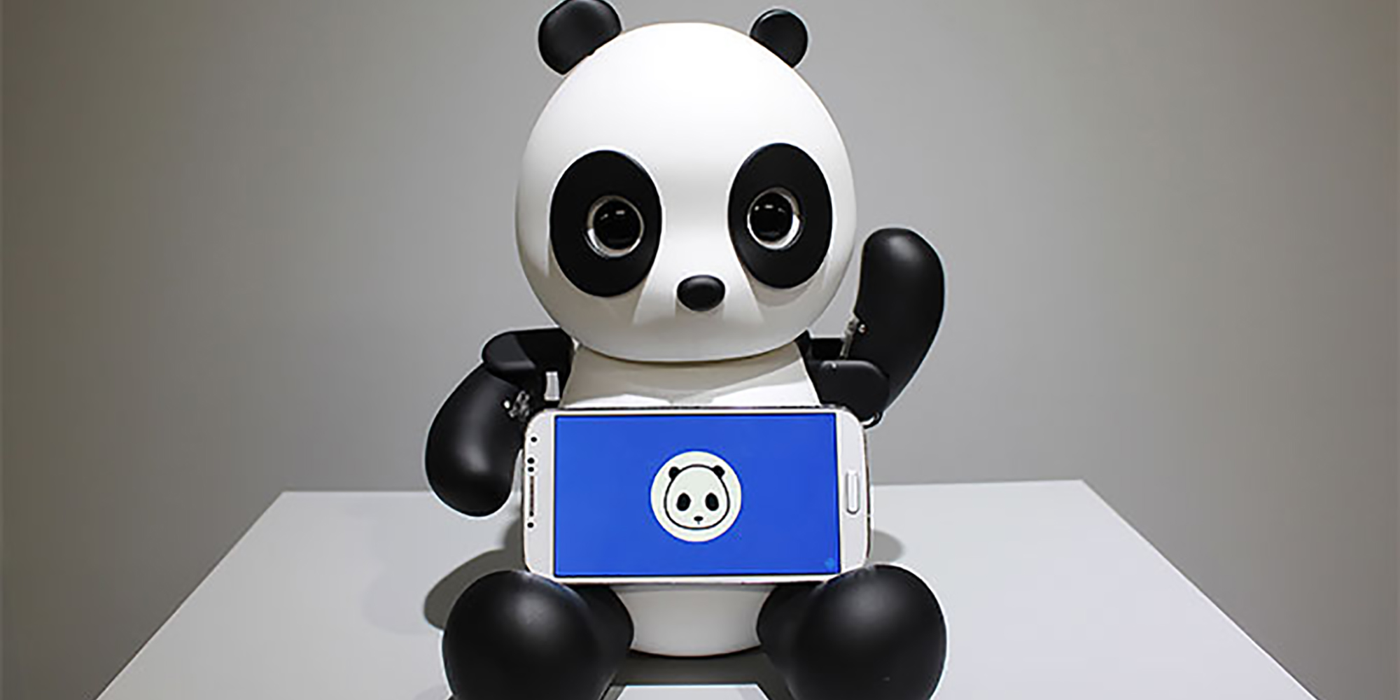 Black and white panda robot with mobile phone in his lap