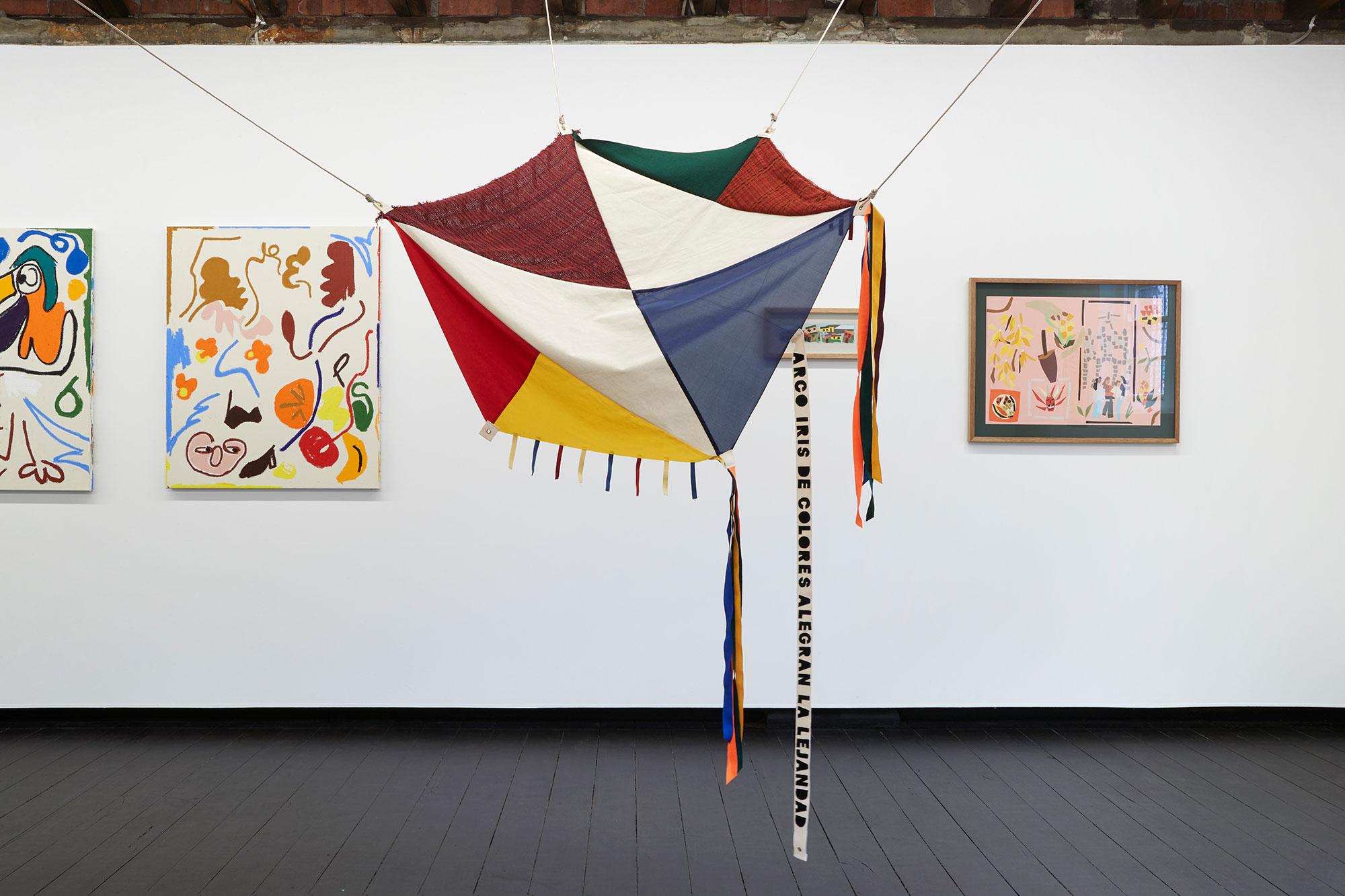 a colourful rainbow kite in an art gallery