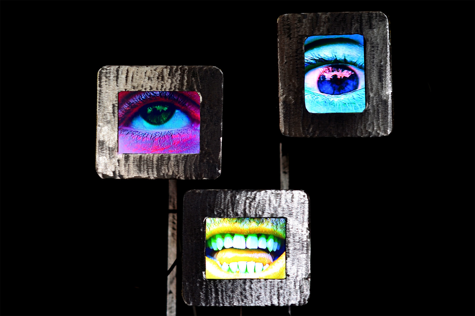 Abstract artwork of a robot with three screens – one with picture of a pink eye, one with picture of a blue eye and one with picture of a yellow mouth on a black background