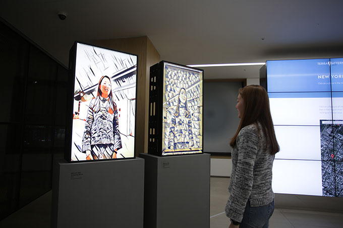 Image of woman looking at her reflection in a mirror installation in a gallery