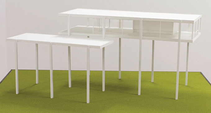 Image of two white structures – one rectangular table with tall legs, one rectangular house with tall legs
